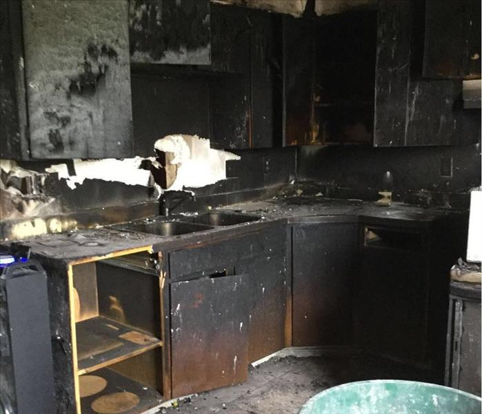 Charred and severely smoke damaged kitchen, in a local apartment.