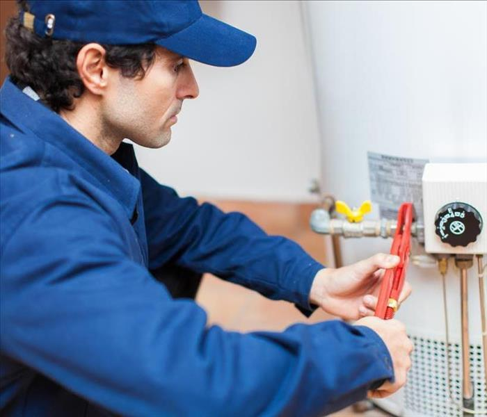Image of a person working on a water heater