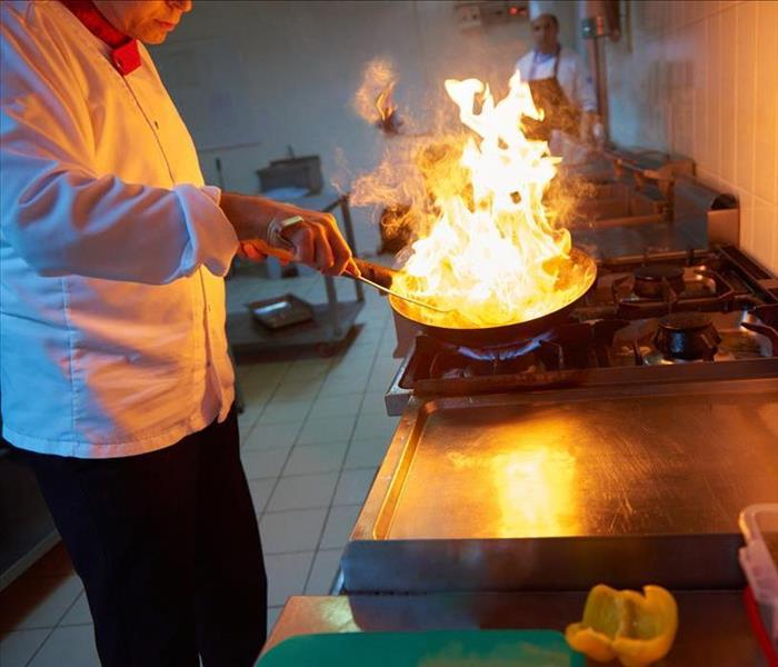 Image of a chef cooking with a frying pan and fire of top.