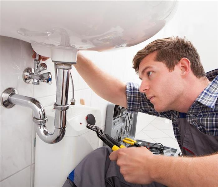 Image of a person performing maintenance on bathroom pipes.