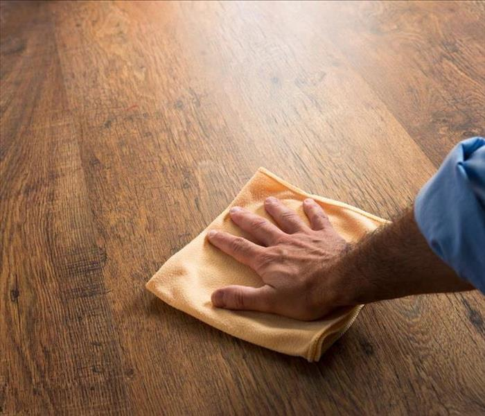 Image of a person mopping a hardwood floor.